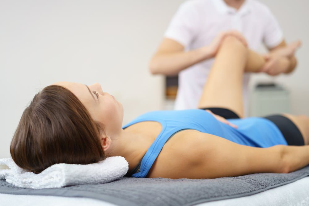 doctor physical therapy on leg female patient
